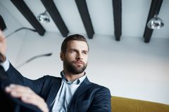 Close-up image of elegant and young businessman in suit who is holding glasses and looking aside thoughtfully. In his modern office. Business style stock photo