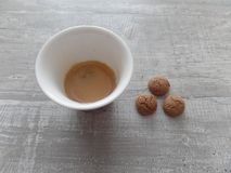 Espresso coffee and biscuits on a wooden grey surface stock images