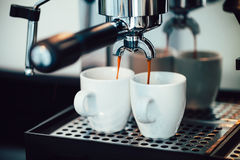 Close up image of espresso pouring into white cups Royalty Free Stock Photography