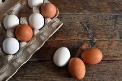 Farm Fresh Organic Eggs. A close up image of farm fresh organic eggs in a paper egg carton on a rustic wooden table royalty free stock photos