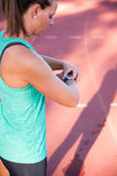 Close up image of a female athlete adjusting her heart rate monitor. A female athlete at a running track adjusts her heart rate monitor before a workout royalty free stock photo