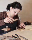 Female Jeweler Working. Close-up image of a female jeweler hammering a piece of metal in her workshop. There is an intended motion blur on the hammer Stock Image