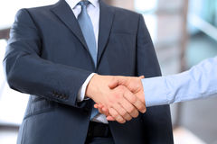 The Close-up image of a firm handshake between two colleagues in office. Royalty Free Stock Photo