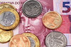 A close up image of a five Brazilian reias bank note with assorted Brazilian coins stock photography