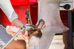 Close up image of four bladed stainless steel speed Boat Engine propeller,Men are checking the bolts.  Stock Image