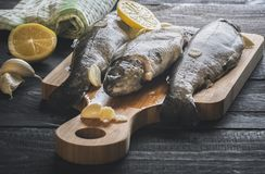 Uncooked fish on a cutting board. Close-up image with fresh trout displayed on a wooden cutting board, seasoned with garlic and lemon slices, on a rustic wooden Royalty Free Stock Photos