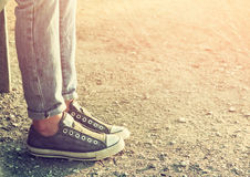 Close up image of girl in sneakers sitting on the bench. Stock Photos