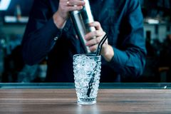 Close-up image of a glass filled full of crash ice and chilled shaker standing on the bar counter. Bartender on the background stock images