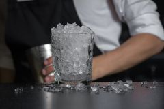 Close-up image of a glass filled full of crash ice. Close-up image of a glass filled full of crash ice, standing on the bar counter, bartender holds chilled royalty free stock photography