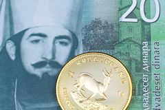 A twenty Serbian dinar bank note with a gold krugerrand coin. A close up image of a golden krugerrand with a green twenty Serbian dinar bank note in macro stock images