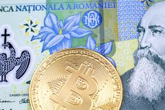 A close up image of a Romanian leu bank note with a gold physical Bitcoin royalty free stock photography