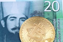 A twenty Serbian dinar bank note with a golden, physical bitcoin. A close up image of a golden physical Bitcoin with a green twenty Serbian dinar bank note in stock photography