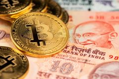 Close up image of gplden Bitcoin with Indian Rupee banknotes. Bitcoin on India Rupee Cryptocurrency against money from India stock photo