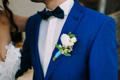 Close-up image of a groom in a blue tuxedo with White boutonniere. Boutonniere on the groom`s jacket. Artwork. Selective focus on the flower royalty free stock image