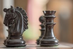 Close-up image of hand carved, ebony wooden chess pieces at the start of a chess match. Royalty Free Stock Image
