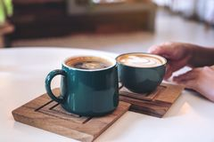 A hand holding a green coffee mugs in cafe. Close up image of a hand holding a green coffee mugs in cafe stock photography