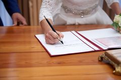 Groom and bride register marriage close up. Close-up image of hands of newlywed couple signing marriage registration form. start of family Stock Photo