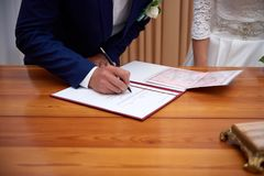 Groom and bride register marriage close up. Close-up image of hands of newlywed couple signing marriage registration form. start of family Royalty Free Stock Photos