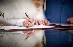 Groom and bride register marriage close up. Close-up image of hands of newlywed couple signing marriage registration form. start of family Royalty Free Stock Images