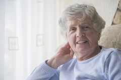 Happy senior woman indoors smiling Royalty Free Stock Image