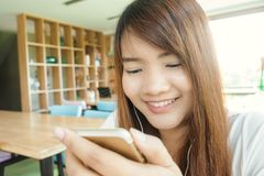 Close-up image of hipster girl sitting at vintage cafe and using modern smarphone, female hands typing message on mobile phone. Royalty Free Stock Photo
