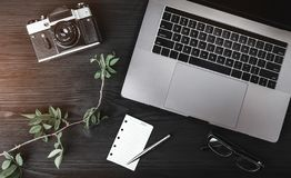 Close-up image of laptop, photo camera, eyeglasses, rose branch and white sheet on black wooden table royalty free stock image