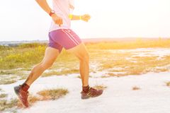 Legs of man running on sandy ground Royalty Free Stock Image