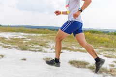 Legs of man running on sandy ground. Close up image of legs of man running on sandy ground royalty free stock photography