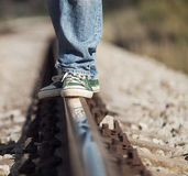 Close up image legs in sneackers on the railway Royalty Free Stock Photo