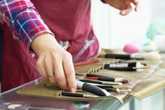 Close-up image of make-up artist hand choosing brush from the set. royalty free stock photography