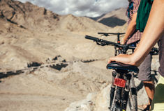 Close up image man hand on bicycle saddle. Two maountain bikers Stock Photo