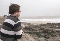 Man in his late twenties looking out towards the sea on a windy day. Close up image of a man in his late twenties looking out towards the sea on a windy day Stock Image