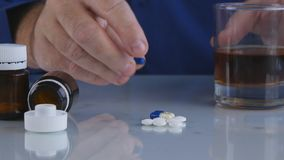 Close Up Image with Man Taking Pills and Drinking Alcohol stock photos