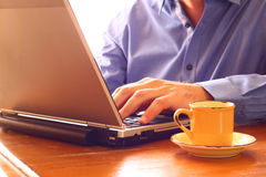 Close up image of man using laptop next to cup of coffee. retro style image. selective focus Stock Photo