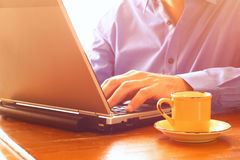 Close up image of man using laptop next to cup of coffee. retro style image. selective focus Stock Images