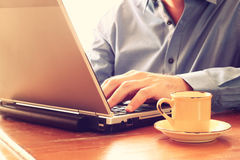 Close up image of man using laptop next to cup of coffee. retro style image. selective focus Stock Photos