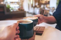 A man and a woman clinking green coffee mugs in cafe. Close up image of a man and a woman clinking green coffee mugs in cafe stock image