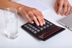Close up image of mans hands using calculator for calculating figures and making financial report. Professional accountant keeps royalty free stock images