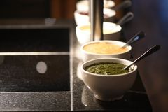 Close up food photography of a line of sauces in bowls as side dishes for roast dinners with focus on mint sauce. A close up image of mint sauce in a white bowl Royalty Free Stock Images