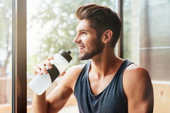 Close up image of model in gym. With bottle. Near the window royalty free stock images