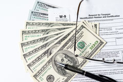 Close up image of money,$100 bills,W-9 form,glasses and a pen stock image