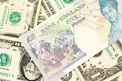 A UK five pound note on a background of one dollar bills. A close up image of a multicolored five pound note from the United Kingdom on a background of one stock photo