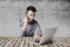 Close up image of multitasking business man using a laptop and mobile phone Stock Images