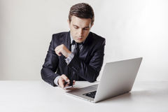 Close up image of multitasking business man using a laptop and mobile phone Stock Photography