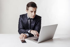 Close up image of multitasking business man using a laptop and mobile phone Stock Photo