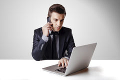 Close up image of multitasking business man using a laptop and mobile phone Royalty Free Stock Image
