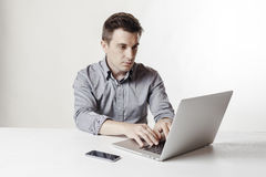 Close up image of multitasking business man using a laptop and mobile phone Royalty Free Stock Photography