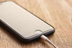 Close up image of the new apple iphone7. PHARE, THAILAND -FEBRUARY 23, 2018: close up image of the new apple iphone7 with the charging cable on the wooden table Stock Images