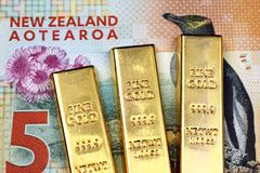Close up image of a New Zealand five dollar bill with three small ingots in macro stock images