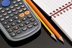 Desk with Stationery Objects. Close up Image of a Notebook, Two Pencils and a Calculator on a Desktop with Black Glass Stock Photo